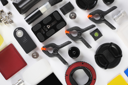 adapters: Workplace of the photographer. Photoaccessories set - lens cap, filters, frames, adapters, eyecups, remote shutter control, lens pen, flash diffuser, brush, bubble level, tripod, background clamps, macro tube, reflector.