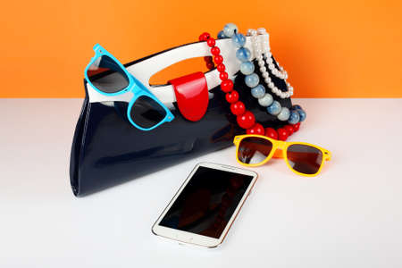 Womens Fashion Accessories. Your style - sunglasses, handbag and mobile phone are decorated with a beads and a pearl necklace. Stock Photo