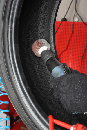 vulcanization: Car service: Tyre repair. The worker repair of tire - Vulcanization Stock Photo