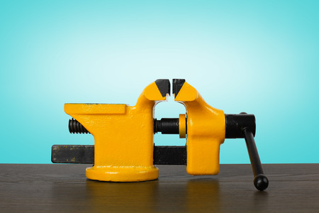 constrict: The metalwork tool - Yellow with black a vise on a wooden table and a blue background.