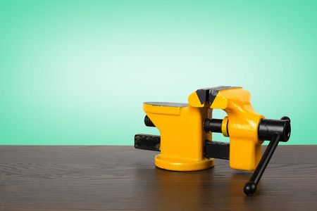 vise: The metalwork tool - Yellow with black a vise on a wooden table and a green background.