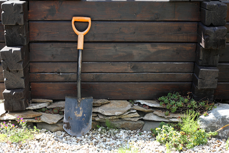 water well: Garden - Shovel at a brown timbered water well Stock Photo