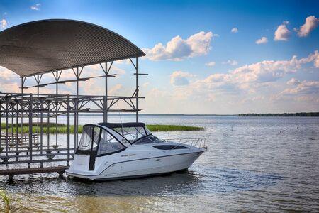 Boats parking - De moderne motorboot op het afmeren op bewolkte de hemel een achtergrond