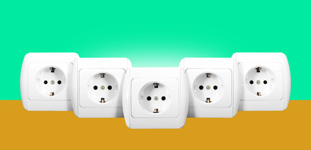 grounding: Electrical grid - The five white electric socket with grounding on a green and orange background.