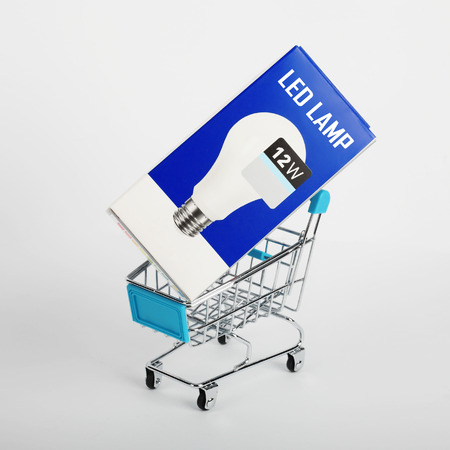 carretilla de mano: Electrical grid - LED Lump on the cart for purchases on a white background. Foto de archivo