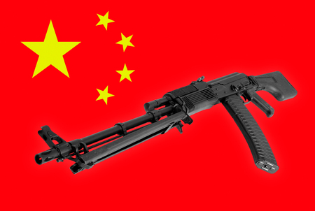 Weapon - A close up black Assault rifle to the China of a flag background. Stock Photo