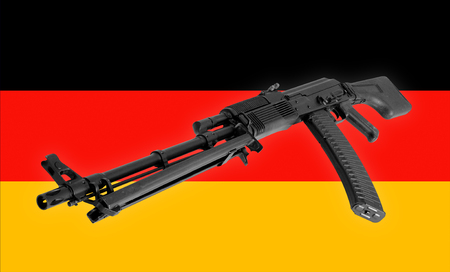 Weapon - A close up black Assault rifle to the Germany of a flag background.