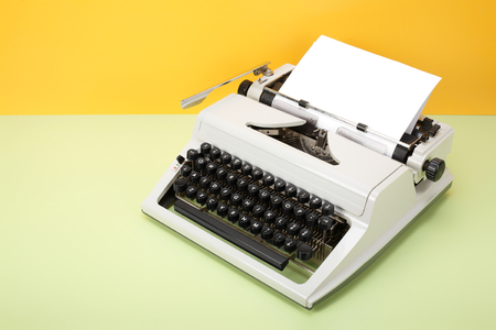 Vintage objects - Retro Typewriter on a yellow background and a green table. Stock Photo