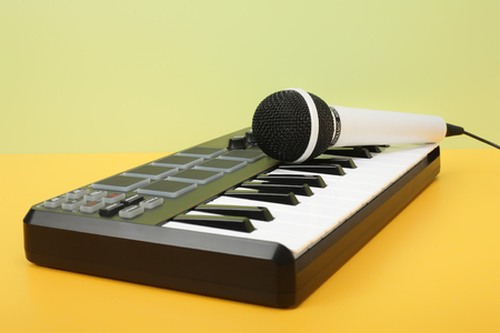 remix: Musical instrument - MIDI keyboard and vokal microphone for a karaoke on a flavovirent background.