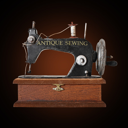 old items: The image of the antique sewing machine on dark brown background.
