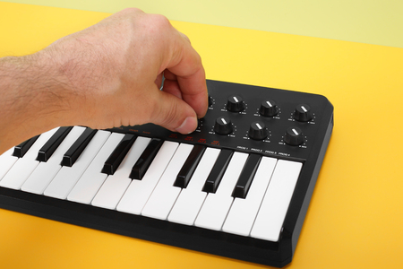 music background: Musical instrument - Hand control MIDI keyboard on a flavovirent background.