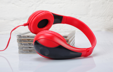music background: Musical equipment - Red headphone and music CD on a white background. Isolated