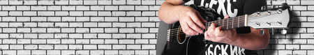 Music - black electric acoustic guitar player chord 7maj5 brick wall closeup.
