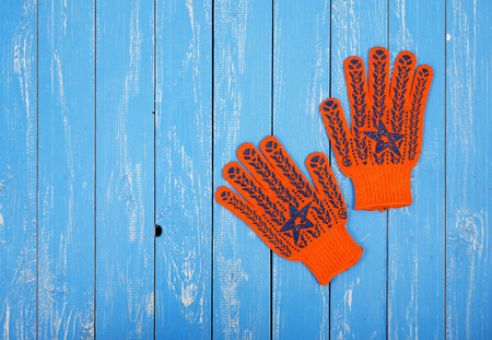 Construction, repair, tools - Orange Working Gloves on a blue wooden background.