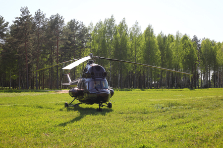 Aircraft - Big Brown helicopter on the parking against the wood. Stock Photo