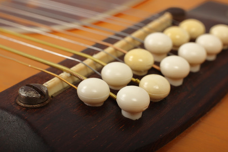Musical instrument - bridge pin twelve-string vintage acoustic guitar. Фото со стока