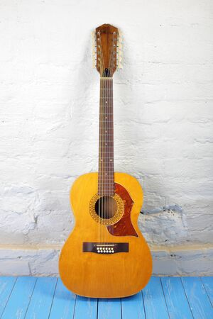 Musical instrument - Front view vintage twelve-string acoustic guitar on a brick background and blue wooden floor.