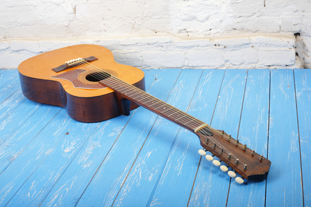 Musical instrument - Vintage twelve-string acoustic guitar on a brick background and blue wooden floor.