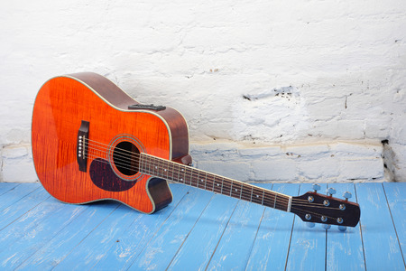 Musical instrument - Orange flame maple acoustic guitar on a brick background and blue wooden floor.