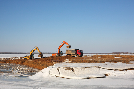 Construction of moorings for the parking of boats - Two excavators behind and dump truck work Stock Photo