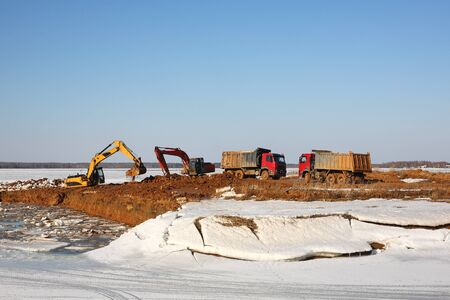 Construction of moorings for the parking of boats - Two excavators behind and dump truck work Banque d'images