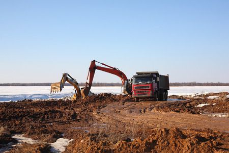 Construction of moorings for the parking of boats - Two excavators behind dump truck work