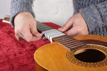 Musical instrument guitar repair and service - Worker preparation pasting of frets for grinding.