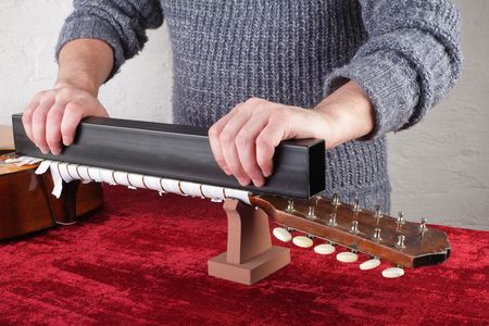 Musical instrument guitar repair and service - Worker grinds guitar neck frets.