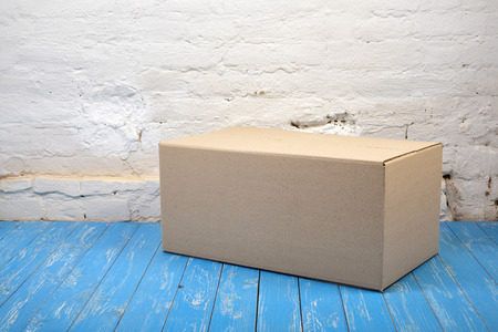 Postage and packing service - Close Package on a blue wood and white brick wall background.