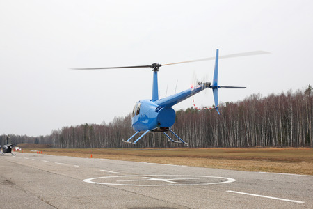 The aircraft - rear view the blue small helicopter makes flight at low height.