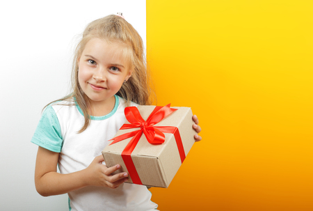 Gifts, shopping and present - Gift box is tied in the girls hands on a yellow and white background.