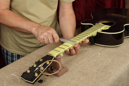 Musical instrument guitar repair and service - Worker sharpen special tool bridge servo nut black acoustic guitar