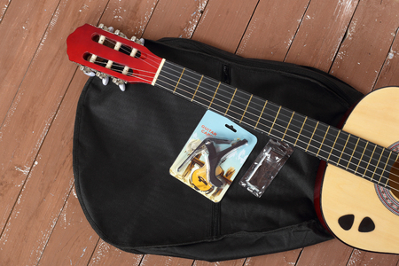 Musical instrument - Classic Guitar, case, capo, key, picks set wood background.