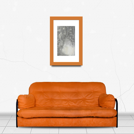 Upholstered furniture in Home interior - Orange modern divan sofa made of cloth in front and Painting picture in a frame of white wall background