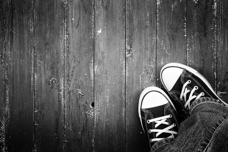 Clothes, shoes and accessories - Top view closeup legs put in gumshoes and jeans top view on a wooden background monochrome 免版税图像