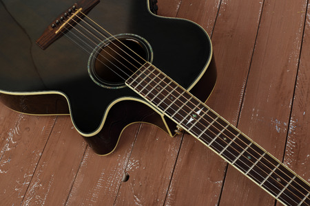 Musical instrument - Fragment brown cutaway acoustic guitar on a wood background. Stock Photo