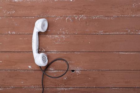 Teléfono vintage auricular blanco sobre un fondo de tablón con textura de madera marrón antiguo retro Foto de archivo