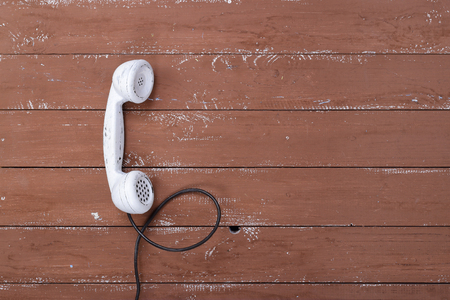 White handset vintage phone on a retro old brown wood textured plank background Stockfoto