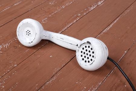 White handset vintage phone on a retro old brown wood textured plank background Reklamní fotografie