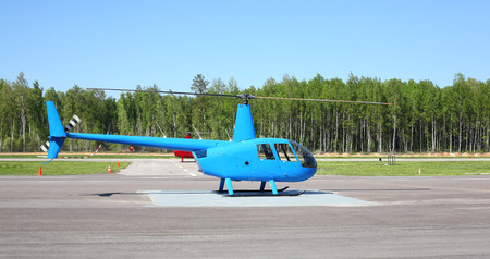 Aircraft - Small blue helicopter on the parking against the wood and sky.