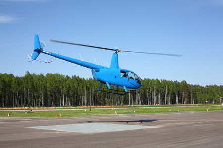 The aircraft - blue helicopter makes flight at low height.