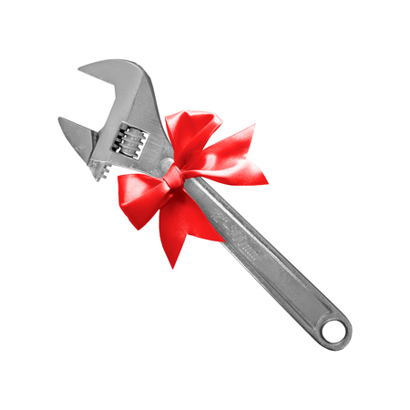 Construction, repair, tools - Gift adjustable spanner a red bow on a white background.  It is isolated, the worker of paths is present.