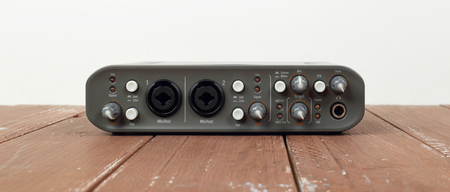 Music and sound - front view interface sound card on a white and wooden background.