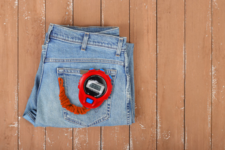 Clothes, shoes and sport - Top view blue jeans and Red Stopwatch on a wooden background
