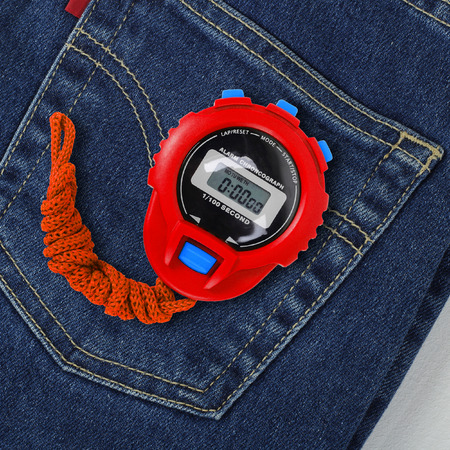 Clothes, shoes and sport - Top view blue jeans pocket and Red Stopwatch closeup