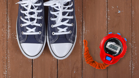 Clothes, shoes and sport - top view fragment closeup pair blue gumshoes and Red Stopwatch on a wooden background Imagens