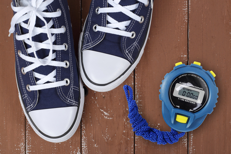 Clothes, shoes and sport - top view fragment closeup pair blue gumshoes and Stopwatch on a wooden background