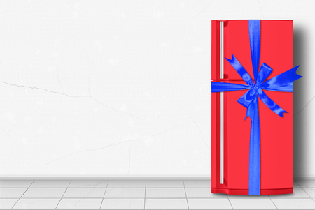 Major appliance - Red refrigerator gift tied blue bow in front on a white wall background