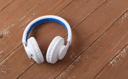Musical equipment - White blue wireless headphone on a wooden background. 스톡 콘텐츠