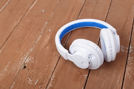 Musical equipment - White blue wireless headphone on a wooden background. Imagens